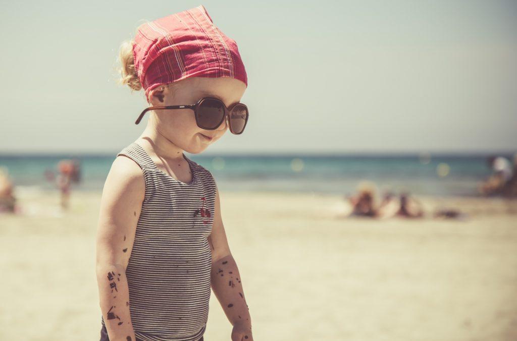 ビーチでサングラスをかけて立っている男の子