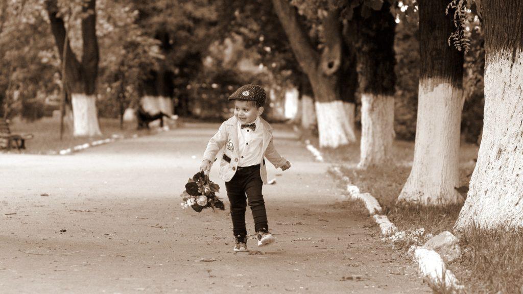 お洒落をして、花束片手に歩いている子ども
