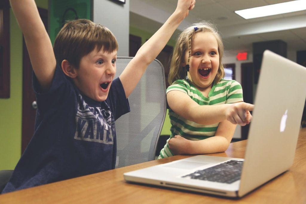パソコンを見ながら喜んでいる男の子と女の子