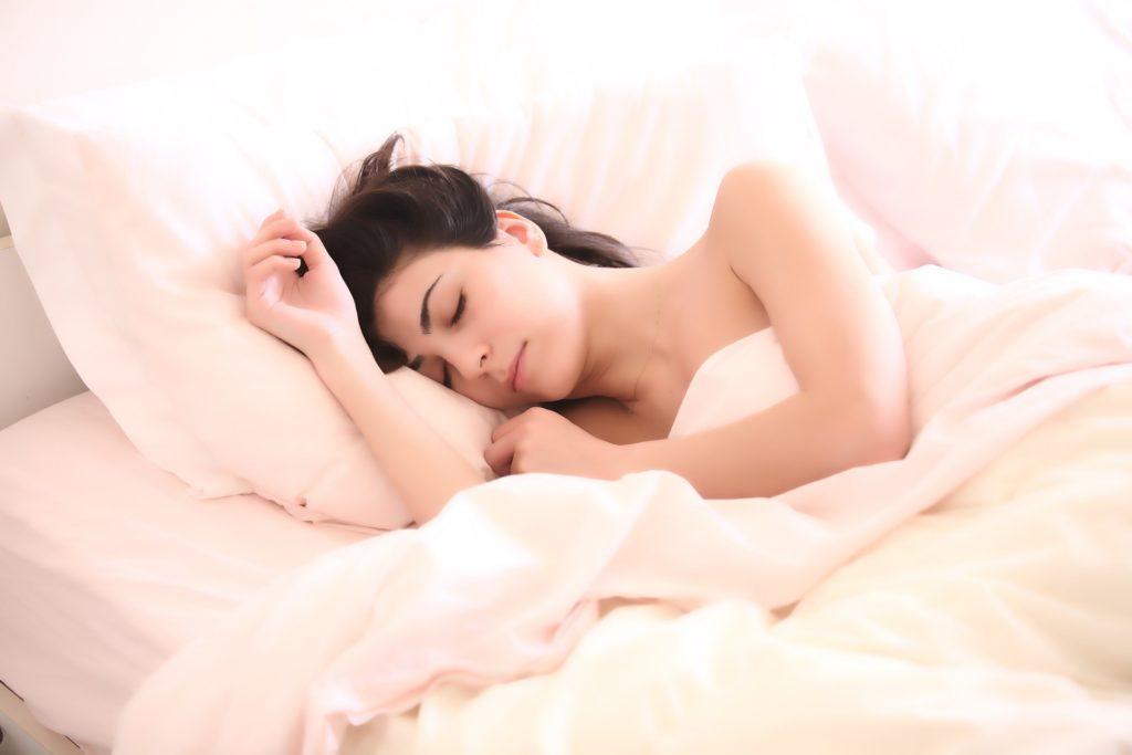 美肌になるためにベッドで睡眠をとっている女性
