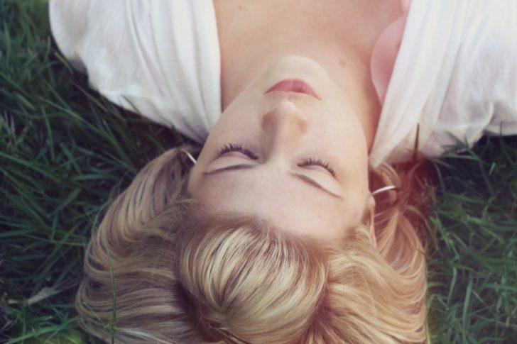 目を閉じて横になっている外国人女性