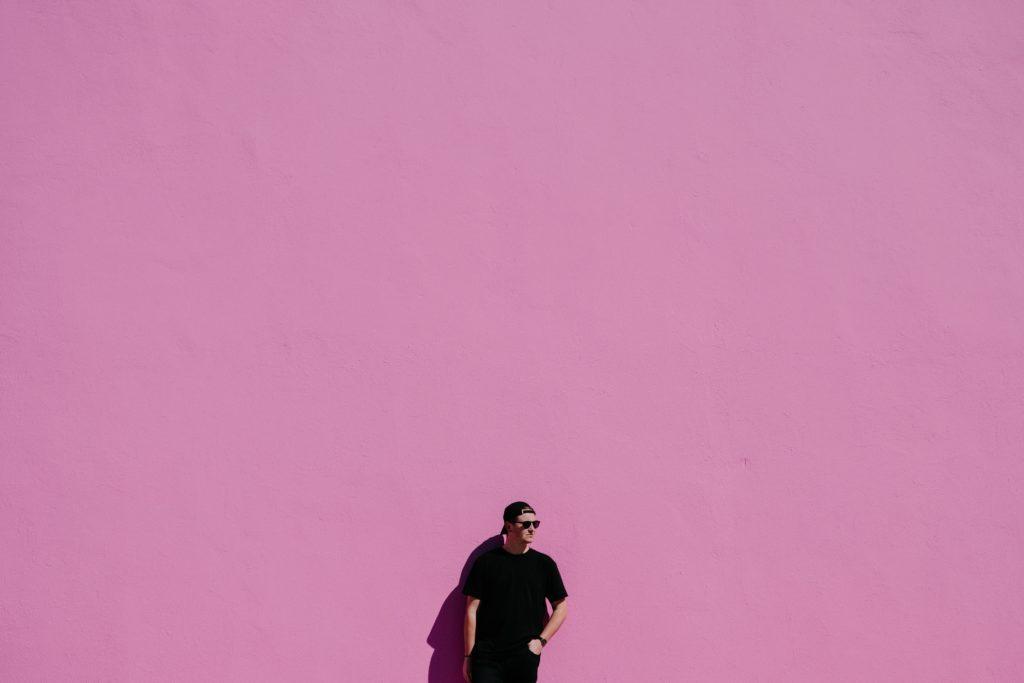 ピンクの壁の前に立っているカッコいい外国人男性