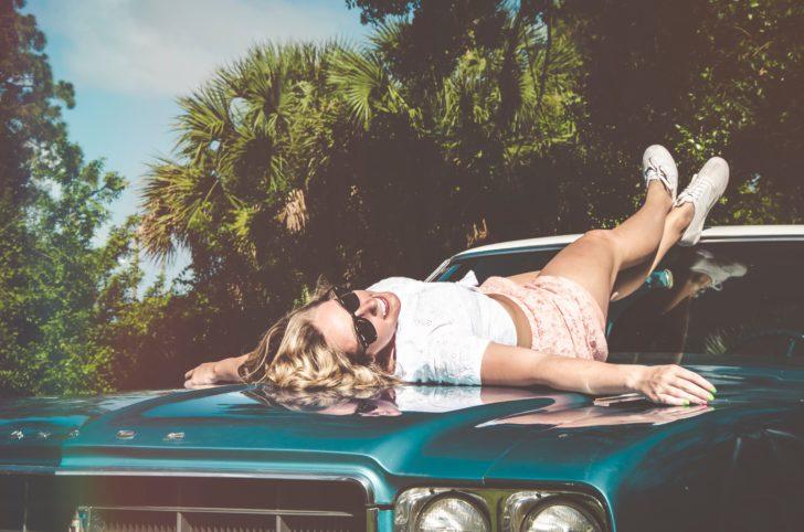 車のボンネットの上で横になっている外国人女性