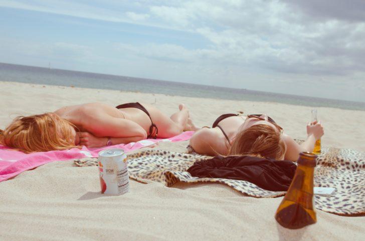 ビキニを着てビーチで横になっている女性