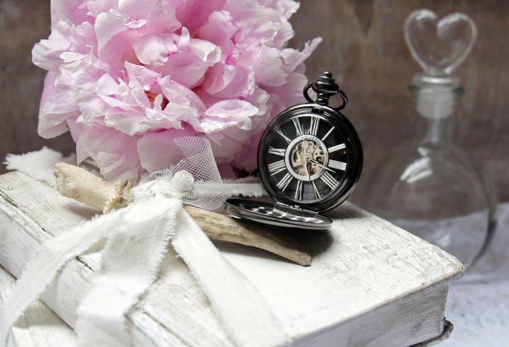 時間を刻む懐中時計とピンクの花束