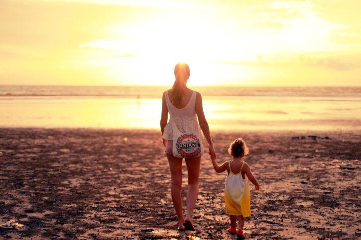 子どもと手をつないでビーチを歩くお母さん