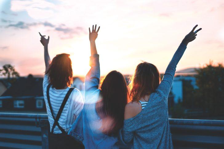 楽しそうに片手を上げている女性3人の後ろ姿