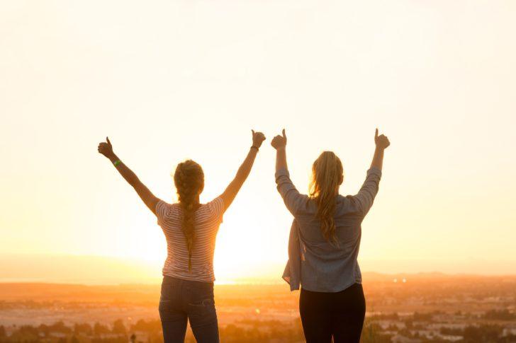 夕焼けに向かって親指を立て、両手を上げている2人の外国人女性