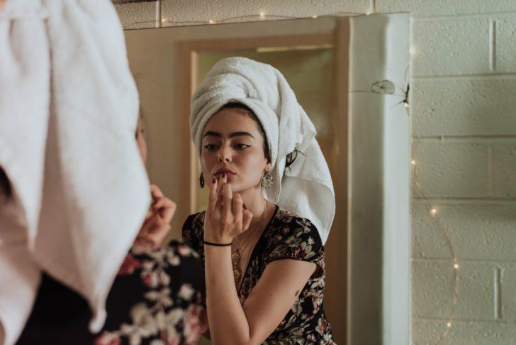 鏡を見ながらスキンケアをする外国人女性