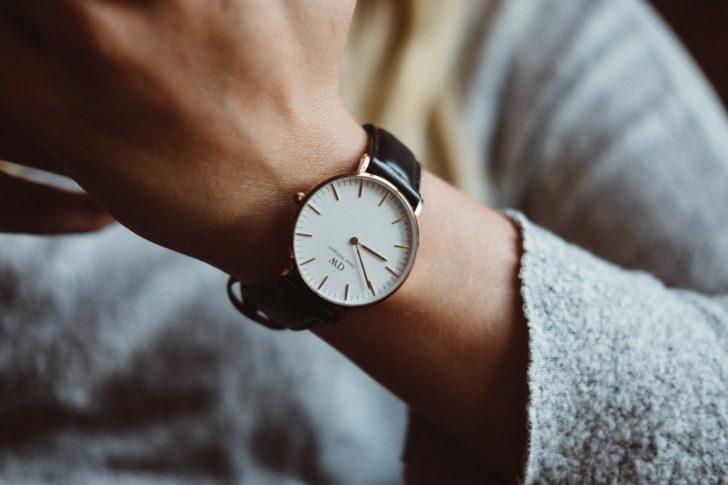 女性の腕に付けられた時計が時間を刻んでいる