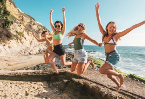 女の子4人がビーチでジャンプ